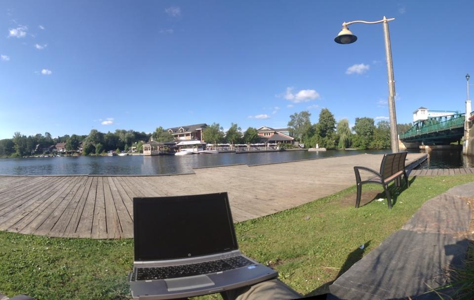 Working from a bench on the edge of the Muskoka River